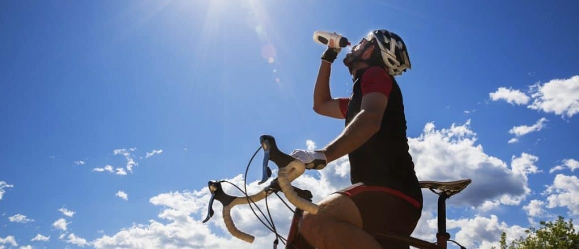 Cyclist resting and drinking isotonic drink.